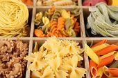 Colorful pasta in wooden box, close-up