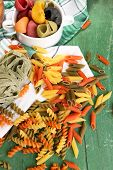 Variety of colorful pasta on wooden background