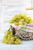 Ripe grapes in metal basket with napkin on wooden table on light background