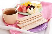 Slices of fruits with crispbreads on plate and cup of tea on wooden tray close up