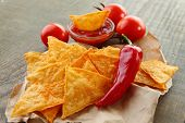 Tasty nachos, red tomatoes and chili pepper on paper, on wooden background