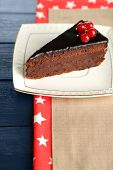Chocolate cake with fresh berries on plate, on color wooden background