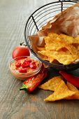 Tasty nachos, red tomatoes and chili pepper in basket on wooden background