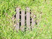 foto of manhole  - Metal rusty manhole cover drainage system in the midst green grass - JPG