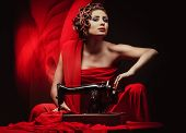 beautiful young pinup woman with sewing machine in red material