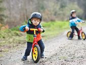 Two Active Little Sibling Boys Having Fun On Bikes In Forest