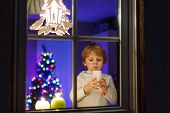 Little Boy Standing By Window At Christmas Time