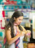 Cheerful elegant young woman testing cosmetics in a store