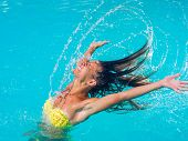 Attractive fit young tanned girl throwing wet hair back in swimming pool
