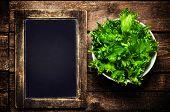 Fresh Green Lettuce  Salad On Blank Vintage Slate Chalk Board On Wooden Table