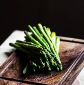 Bunch Of Fresh Green Asparagus Spears Tied With Twine On A Rustic Wooden Table