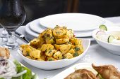 stock photo of batata  - Spicy potato cut in cubes and fried - JPG