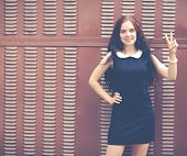 Beautiful Brunette With Long Hair In A Short Black Showing Two Fingers Up Near Metallic Brown Fence.