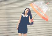 Beautiful Brunette With Long Hair In A Short Black With An Umbrella In Her Hands Looking At The Sky
