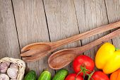 Fresh ripe vegetables and utensils on wooden table with copy space
