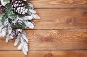 Christmas fir tree with snow on rustic wooden board with copy space