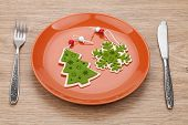 Christmas decor on plate and silverware over wooden table background