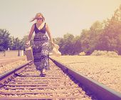 a girl walking down train tracks with a suitcase and hat done with a vintage retro like instagram f