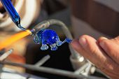 TEL AVIV, ISRAEL - FEBRUARY 11, 2012: Delicate work of the glass blower. The Artist-glass blower produces a graceful tiny figure of an elephant from color glass