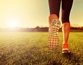an athletic pair of legs on grass during sunrise or sunset - done with a soft vintage instagram lik