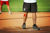 a man's legs on a baseball or softball field with a big scrape