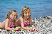 Two Pretty Little Girls Lying On Stony Beach Near Sea