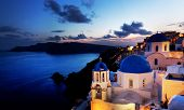 Oia town on Santorini island, Greece at night. Traditional and famous churches with blue domes over the Caldera, Aegean sea