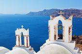 Oia town on Santorini island, Greece. Traditional bells and crosses over the Caldera, Aegean sea