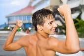 Teenager Boy Standing Near Hotel On Resort In Evening
