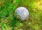 Grunge Football Or Soccer Ball On A Green Lawn