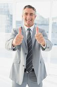 Businessman looking at the camera giving a thumbs up