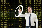 Young serious businessman pointing to a white clock against black airport departures board with yell