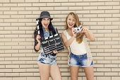 Two beautiful and young girlfriends holding a clapboard, in front of a brick wall
