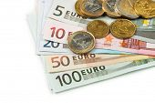 Euro coins and banknotes on white background