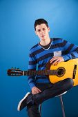 Teenager holding a classic guitar with blue background