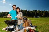 Young couple preparing sausages on a grill outdoors
