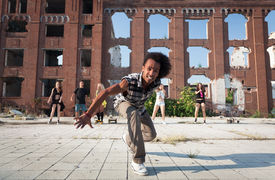 picture of cheeky  - Happy energetic African American street dancer lunging at the camera with a cheeky smile as he performs his hip hop dance routine in an urban square - JPG