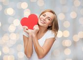 happiness, health, people, holidays and love concept - smiling young woman in white t-shirt holding red heart over lights background