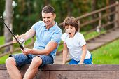 foto of exciting  - Happy father and son fishing together while little boy looking excited and keeping mouth open - JPG