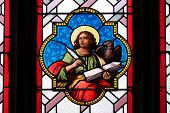 GRAZ, AUSTRIA - JANUARY 10, 2015: Saint John the Evangelist, stained glass window in Parish Church of the Holy Blood in Graz, Styria, Austria on January 10, 2015.