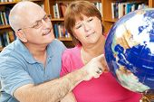 Adult students in library using a globe to study geography.