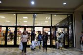 People Walk Out Of Macy's Store With Shopping Bags On Grey Thursday