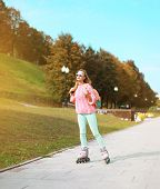 Fashion, Extreme, Youth And People Concept - Pretty Stylish Hipster Girl Rollerblading In The City P
