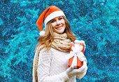 Christmas And People Concept - Happy Pretty Woman In Red Hat With Box Gift Near Christmas Tree In Wi
