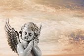 Sad praying angel on an orange heaven background for a condolence card.