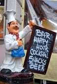 Menu board in restaurant and bar. Chef statue holding menu board.