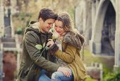 picture of candid  - candid portrait of beautiful European couple with rose in love kissing on street celebrating Valentines day with passion sitting on city park in winter urban background - JPG
