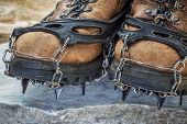 old hiking boots with trail crampons on stone background