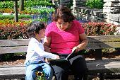 Hispanic Grandmother reading with her grandson