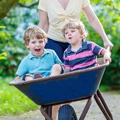 Two Little Boys Having Fun In A Wheelbarrow Pushing By Mother